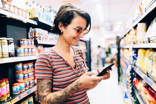 Young woman using mobile phone at market grocery store