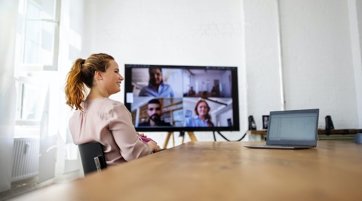 An office meeting room with four staff attending via video.