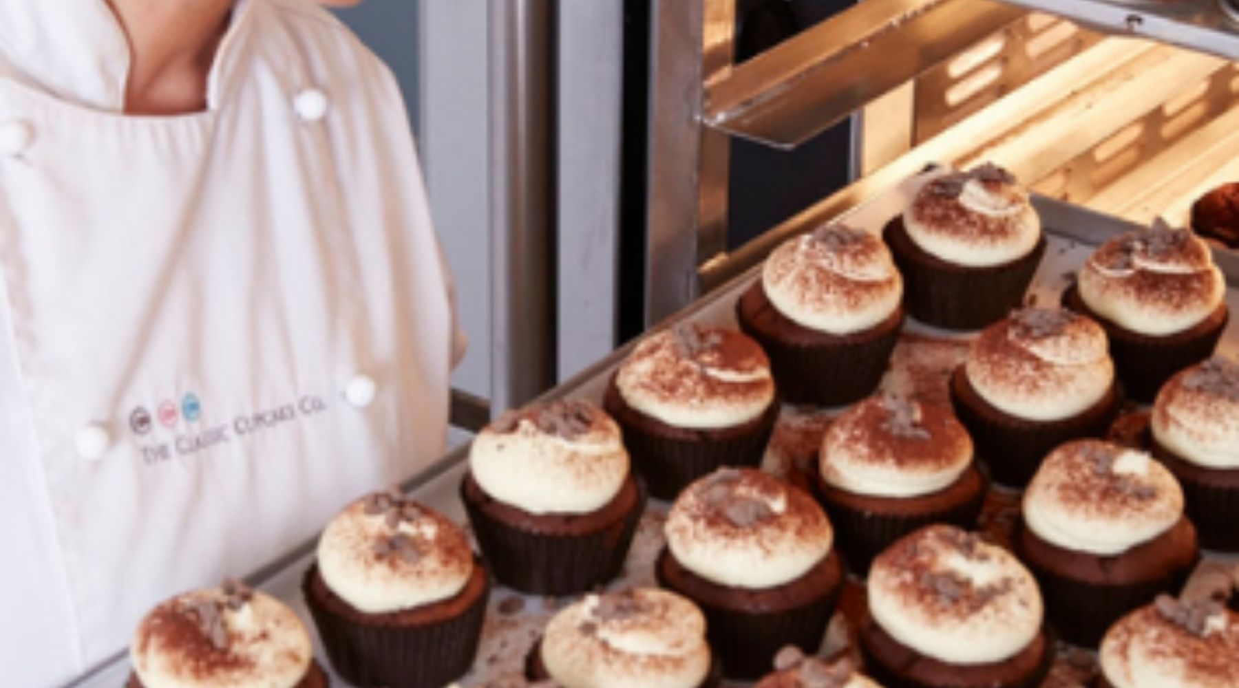 A tray of cupcakes being taken out of the oven.