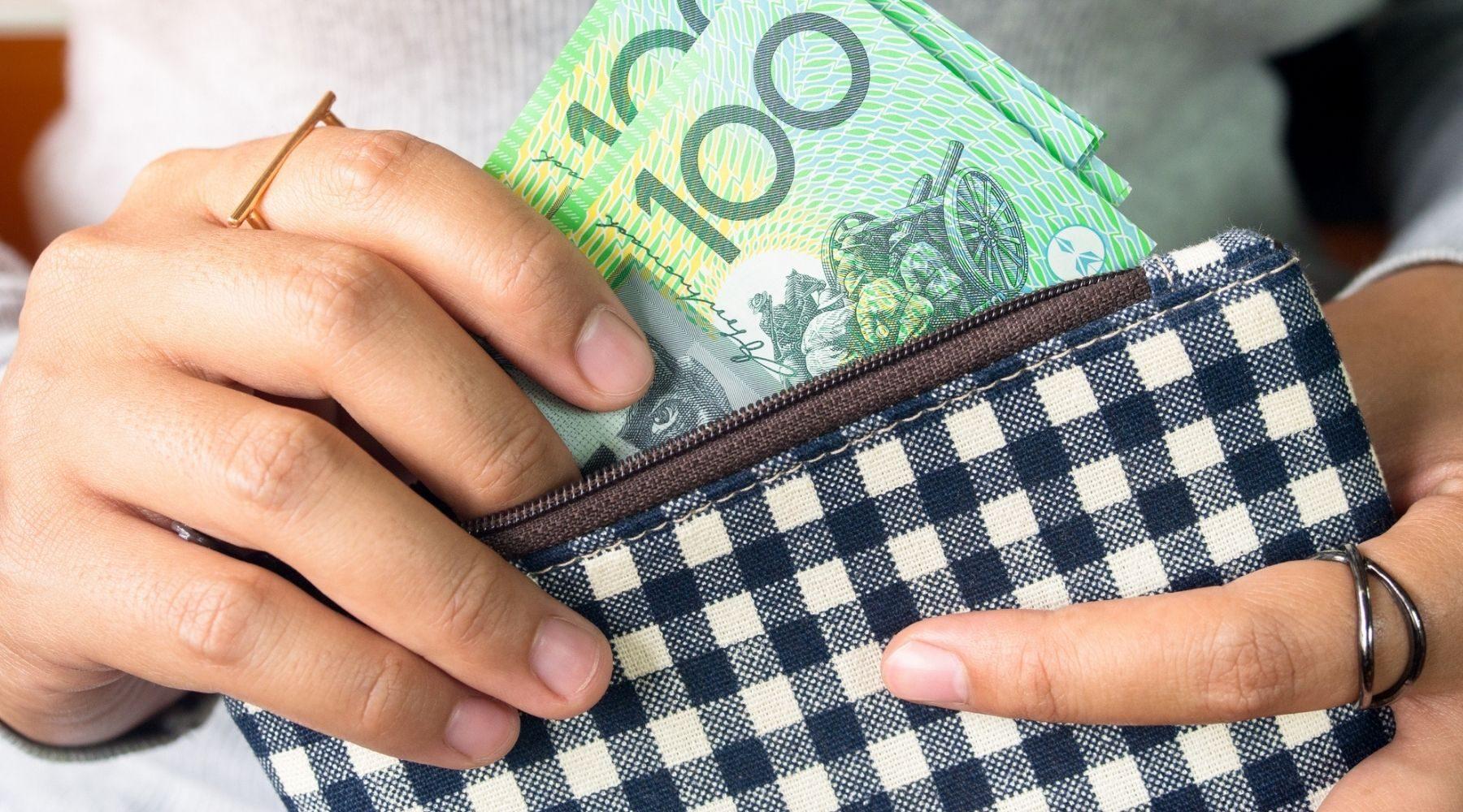A woman holding Australian money.