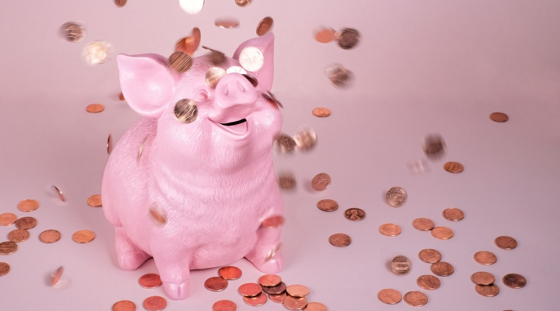 Piggy bank on a pink background, with coins falling around.